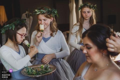 Ślubna sesja zdjęciowa w Paryżu trzech młodych dziewcząt kwiatowych pachnących kwiatami na talerzu