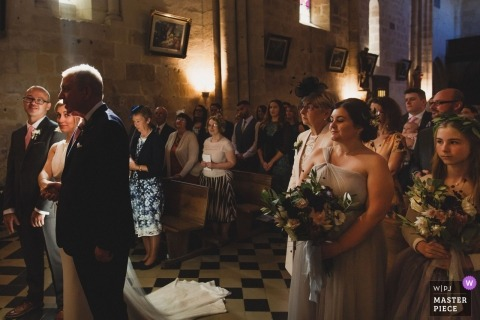 Paris wedding photojournalism image of a bride and guests in beautiful window light during ceremony