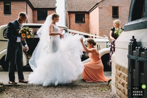Wedding picture of a bride receiving help with her dress after getting out of the car, by Nottinghamshire photographer