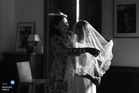 Château de Vaugrigneuse, Ile de France wedding photograph of bride getting help with her veil.
