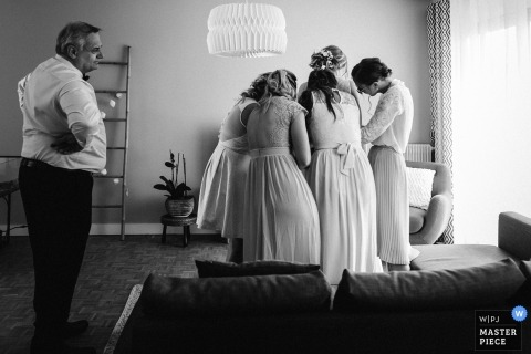 Documentary wedding photography at Il de France of a father patiently watching four bridesmaids help his daughter into her dress