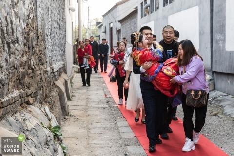 Peking-Hochzeitsfotojournalismusbild des Bräutigams etwas Hilfe erhalten, die seine Braut trägt