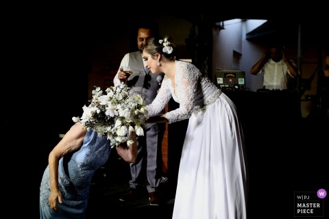 Wedding photo shoot in Patos de Minas with the bride getting help with her bouquet of flowers