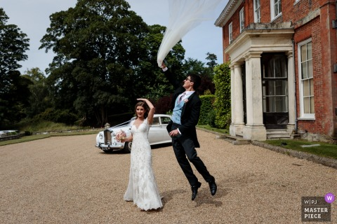 The Brides wayward veil is retrieved by her fast acting husband at Squerryes Court - Photo by a top Kent wedding reportage photographer