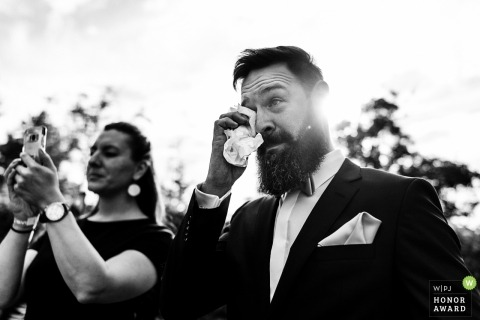 Photographie documentaire de mariage au Landhotel Waldhaus avec un marié barbu essuyant ses larmes au soleil