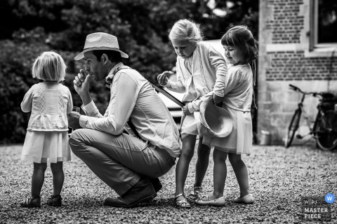 Belgium wedding photo of a man playing with three young girls during the reception