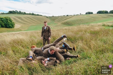 Wellington Barn, Calne UK | groomsmen and ushers pile on top of each other in field