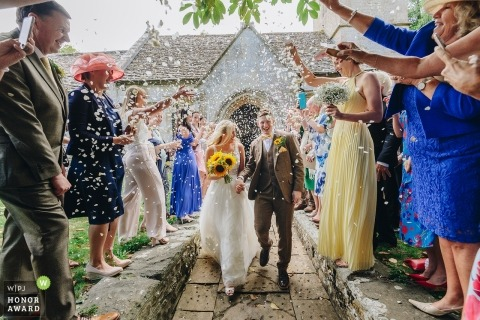 bride and groom leaving church whilst guests throw into the Confetti gauntlet -Calne, UK