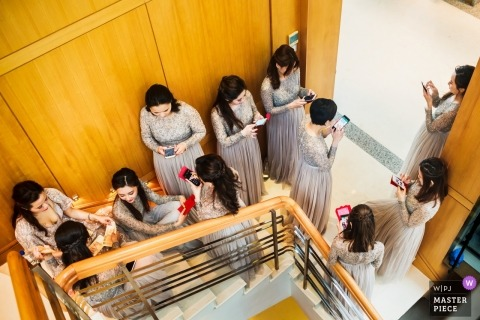 Hochzeitsfotos von Fotografen aus Hongkong - Draufsicht auf viele Brautjungfern in einem Treppenhaus an ihren Telefonen