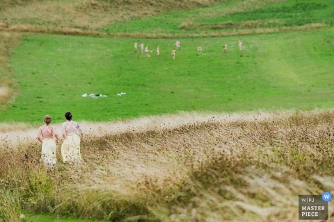 Bridesmaids running in field to take groomsmens clothes | Wellington Barn, Calne UK wedding photography