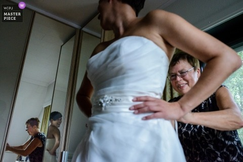 East Flanders wedding photograph of a bride putting on her dress reflected in multiple mirrors
