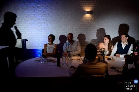 Oost-Vlaanderen bruiloft fotojournalistiek beeld van een paar verlicht tijdens de receptie speeches met schaduwen op de muren