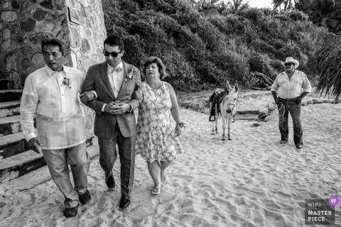 Documentary wedding photograph of the groom being escorted by parents in the sand to his beach ceremony in Puerto Vallarta