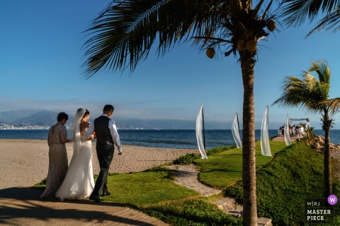 Puerto Vallarta documentary wedding photo of a bride beginning the long walk with her parents to the outdoor beach wedding ceremony under palm trees