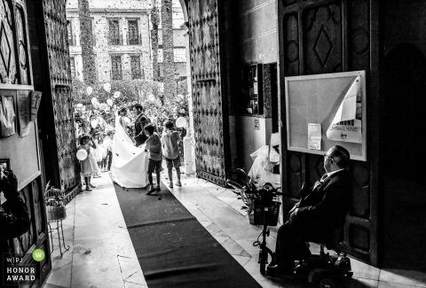 Der Vater der Braut sieht zu, wie das Paar die spanische Kirche verlässt - Hochzeitsfotograf