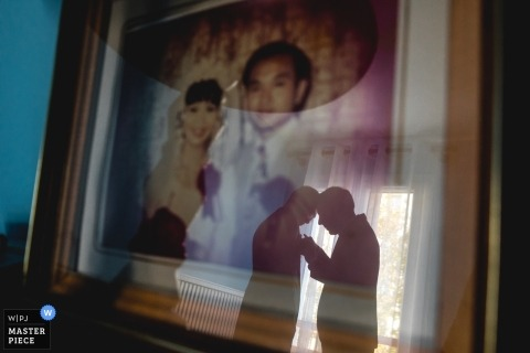 Wedding photo in Paris of two men working on a boutonniere while being reflected in the glass of a wall hanging portrait