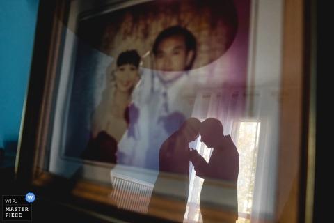 Ślubna fotografia w Paryż dwa mężczyzna pracuje na boutonniere podczas gdy odbijający w szkle ścienny wiszący portret