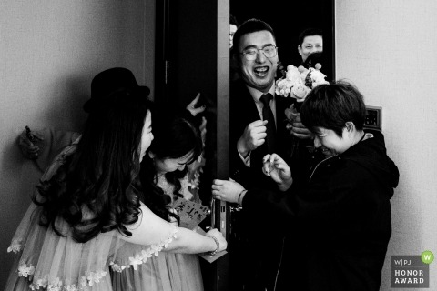 Wedding picture of the groom pushing his way into a room with a blocked door to get to his bride, by Zhejiang photographer