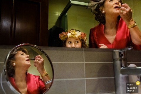 Documentary wedding photograph of a woman applying lipstick in the mirror with a young flower girl watching at Alicante