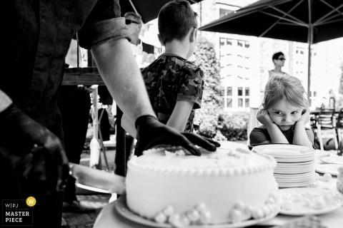 Dokumentalna fotografia ślubna młoda dziewczyna ogląda ciasto wycinane przez personel sprzedawcy w recepcji 's-Hertogenbosch