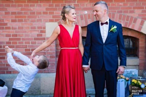 在波兰结婚宴会的婚礼新闻摄影与握有一个小男孩的格但斯克夫妇手