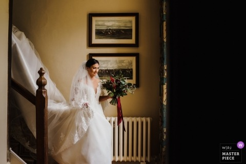 Bruisyard Hall Wedding Photography of bride coming down stairs