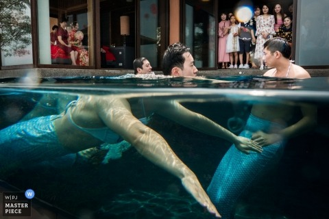 Fujian documentary wedding photo of groomsmen swimming pool with mermaid costumes during Chinese door games