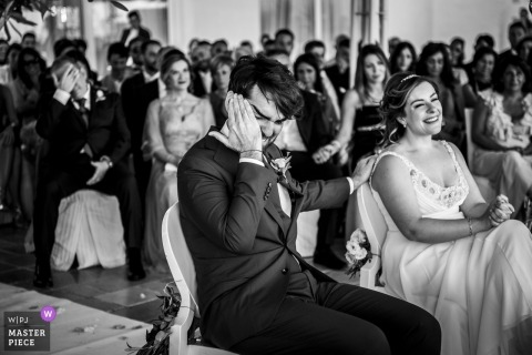 Puglia wedding photo a groom wiping his face during the ceremony with his bride seated next to him