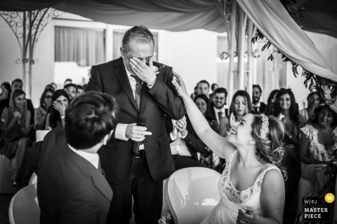 Puglia wedding shoot with a bride comforting her crying father during the emotional reception