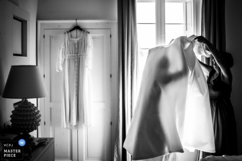 Puglia wedding photo of a bride preparing to put on her dress | wedding photographs in black-and-white