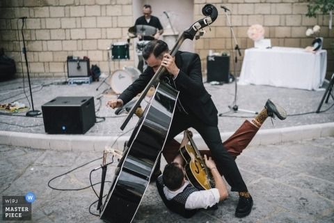 Puglia wedding photo of rowdy musicians by a photographer - guitarist and bass player having fun at the reception