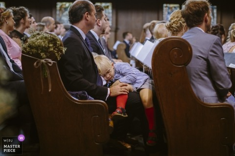 Wedding picture of a small boy in the pews from the long ceremony by Aachen photographer