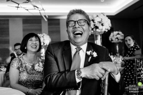 Fotografia di matrimonio di Washington Documentary alla festa di ricevimento di Seattle di un uomo e di altri ospiti che ridono