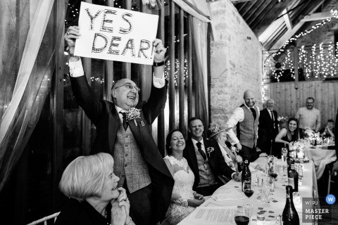 Kingston Country Courtyard, Wareham, UK wedding photograph of guest holding up 'yes dear' handmade sign at the reception.