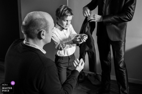 Wedding pictures of a young ring bearer adjusting his shirt cuffs by Saint Junien, France photographer