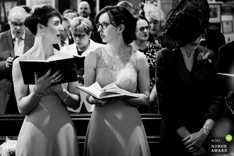 Silverdale wedding photo of bridesmaid singing from the church hymnals | wedding photography for the UK
