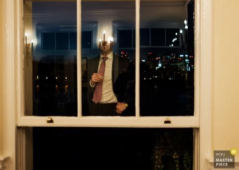 The Trafalgar, London wedding photograph of guest reflected in reception window glass.