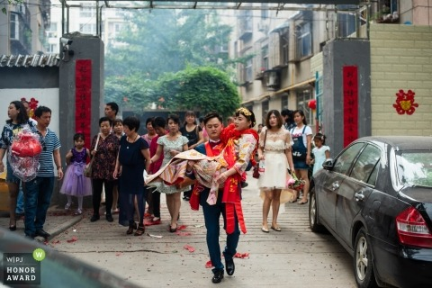 Shaanxi wedding shoot with a groom carrying his new bride as guests follow behind in the streets