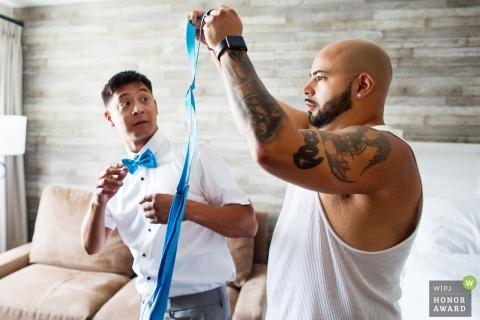 groom looks surprised as groomsmen helps him with suspenders for grand hotel cape may nj wedding