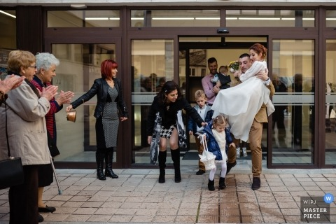 Picture of a groom carrying his new bride and about to be tripped up by a small child - Lovech wedding photographer