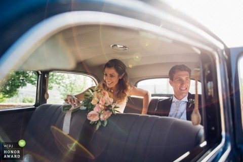 Treviso couple in the back of the getaway car with sun flares after their wedding