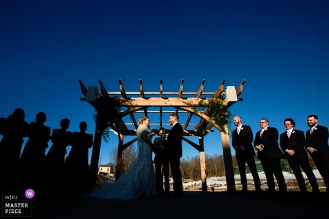 New Jersey wedding photojournalism image of a couple splashed in a great sunlight with silhouettes and blue skies during their outdoor ceremony