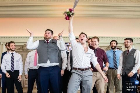 Wedding pictures by New Jersey photographer of the Single men at the reception catching a bouquet