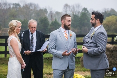 Photo d'un adulte demandant à son meilleur homme les alliances dans The cérémonie, par un photographe de mariage haut du New Jersey