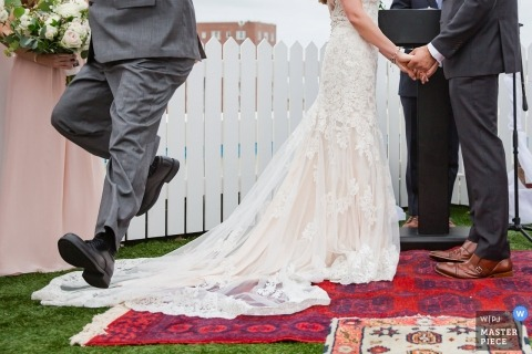 Fotografia ślubna taty w New Jersey przeskakująca przez sukienkę podczas ceremonii plenerowej