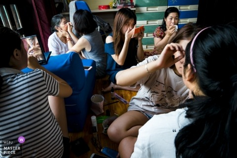 Vietnam wedding photograph of five different women working on their makeup