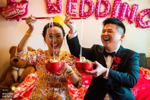 Picture of a couple about to enjoy a bowl of noodles, by a top Fujian wedding photographer