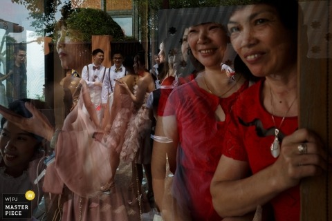 Documentary wedding photograph at Shandong ceremony with guests looking through reflecting glass at the men