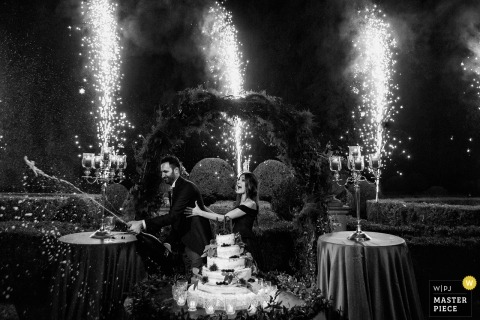 Villa Molin - Italy wedding photograph of bride and groom at wedding cake with fireworks going off behind them.
