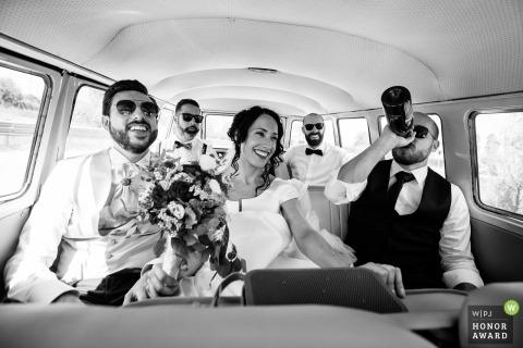 Hochzeits-Foto mit den Venetienpaaren, die mit Freunden innerhalb des Brautpartypackwagens hängen, während ein Groomsman von einer Flasche trinkt